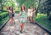 pic of envy  -  joyful girl with the mobile phone and group of envying girls - JPG