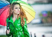 image of redheaded  - Beautiful woman in bright green coat posing in the rain holding a multicolored umbrella - JPG