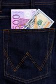 Dollar and euro banknotes in jeans pocket