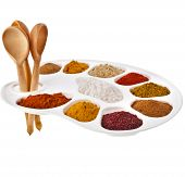 Collection of various color powder spices on a cooking palette with spoons isolated on a white backg