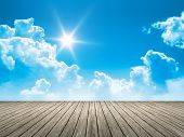 An image of a wooden jetty blue sky sun background