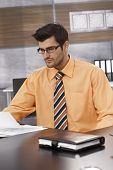 Businessman sitting at desk, working in office, wearing shirt and tie.