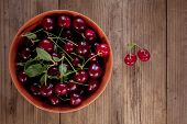 Ripe Cherries With Leaves In Bowl On Old Wooden Rustic Background
