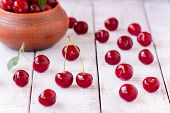 Juicy Ripe Cherry On A White Wooden Background