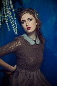 portrait of a beautiful woman with red hair in curly braided hairstyle. wearing a romantic lace dres