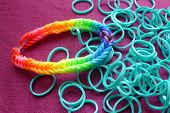 pic of loom  - Loom band bracelet woven in rainbow colors and loose unwoven turquoise loom bands - JPG