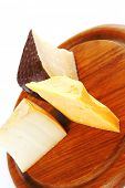 french aged cheeses on dark wooden board