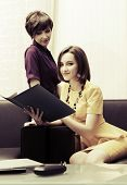 Two young fashion business women with a folder at office