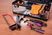 Tools In Tool Box On Wooden Floor