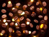 Falling black coffee grain, bean background against black wall and abstract bokeh.