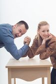 Stylish workmates laughing while playing arm wrestling