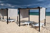 Different Parasols And Sun Loungers On The Empty Beach On Tavira Island Before Storm