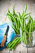 green string beans in glasses, napkin and knife closeup on rustic wooden background