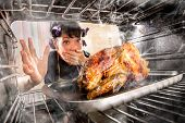 Funny Housewife overlooked roast chicken in the oven, so she had scorched, view from the inside of t