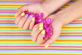 Female hand with stylish colorful nails holding decorative stones, on bright background