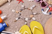 Shape of sun made from sea shells and stones on sand with beach accessories