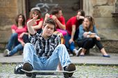 Cool teenager sitting outside with skateboard