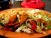 image of mexican food  - Chicken Fajita dinner on plate at a Mexican restaurant in the afternoon sunlight - JPG
