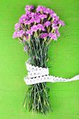 Beautiful bouquet with lace ribbon on wooden background