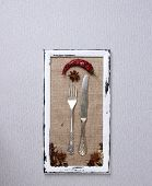 Wooden frame, spices and vintage cutlery  on color background