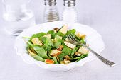 Green salad with spinach, apples, walnuts and cheese on light background