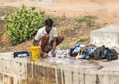 Man Doing Laundry Manually On Concrete Slab Of River Bridge.