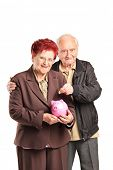 Senior couple putting money into a piggybank isolated on white background