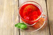 Fruit red tea with wild berries in glass cup, on wooden background