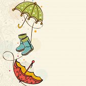 Stylish rainy season concept with colourful umbrellas and boots on beige background.