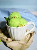 Tasty pistachio ice cream in cup on wooden table, on blue background