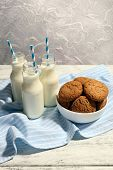 Milk and cookies on table on light grey background