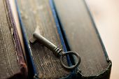 Knowledge, concept image. key to solutions. Old vintage key on old books.