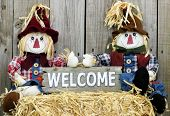 Boy and girl scarecrows sitting on straw bale holding rustic wood welcome sign