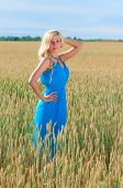 Happy womanin blue dress in golden wheat.