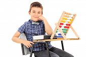 Schoolboy sitting at a desk with an abacus on it isolated on white background