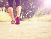an athletic pair of legs running or jogging on a path during sunrise or sunset - healthy lifestyle