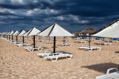 Different Parasols And Sun Loungers On The Empty Beach On Tavira Island Before Storm, Algarve. Portu