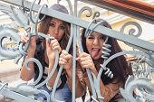 young girls behind metal railings