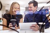 Woman laughs as man shows tablet