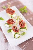 zucchini roll with cream and dried tomato