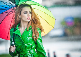 stock photo of rainy weather  - Beautiful woman in bright green coat posing in the rain holding a multicolored umbrella - JPG