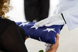 foto of funeral  - active navy representatives giving the US flag to the widow at a veterans funeral