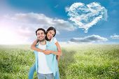 Happy casual man giving pretty girlfriend piggy back against cloud heart