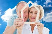 Happy older couple holding house shape against cloudy sky