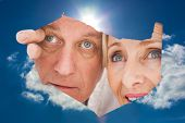 Older couple looking through rip against blue sky with clouds and sun