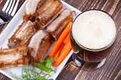 Glass of beer grilled pork ribs and fresh carrot on wooden background