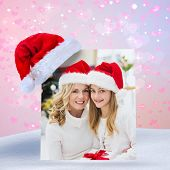 Festive mother and daughter smiling at camera against digitally generated girly heart design