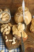 Tasty sandwiches and jar with fresh peanut butter on wooden background
