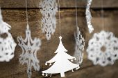 Soft focus Christmas decorations snowflake ,christmas tree paper hanging over wooden background