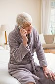 Senior man making a phone call on bed at home in bedroom